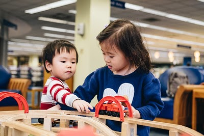Two preschoolers playing at the train table