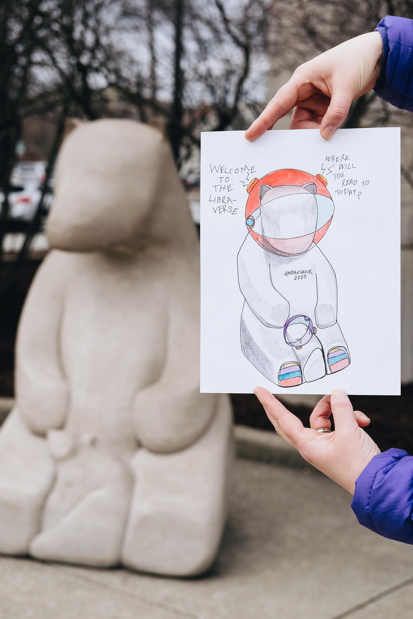 A photo of Bicentennial Art Contest winner Rebecca Mueller's drawing held in front of the Friends of the Library bears.