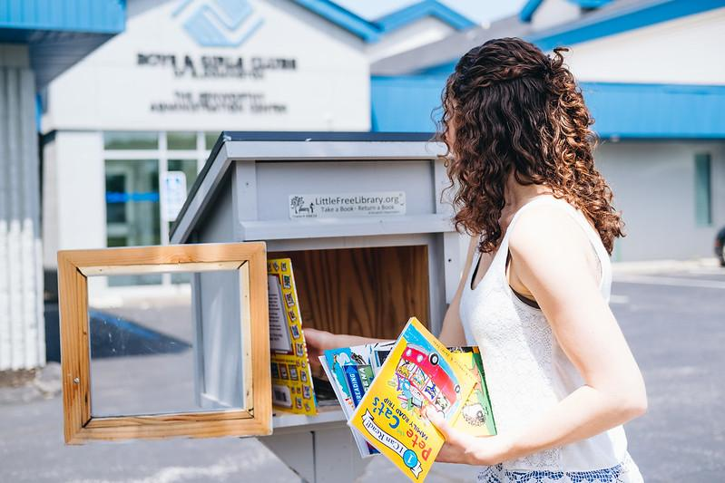Staff Filling Little Free Library Box with Books