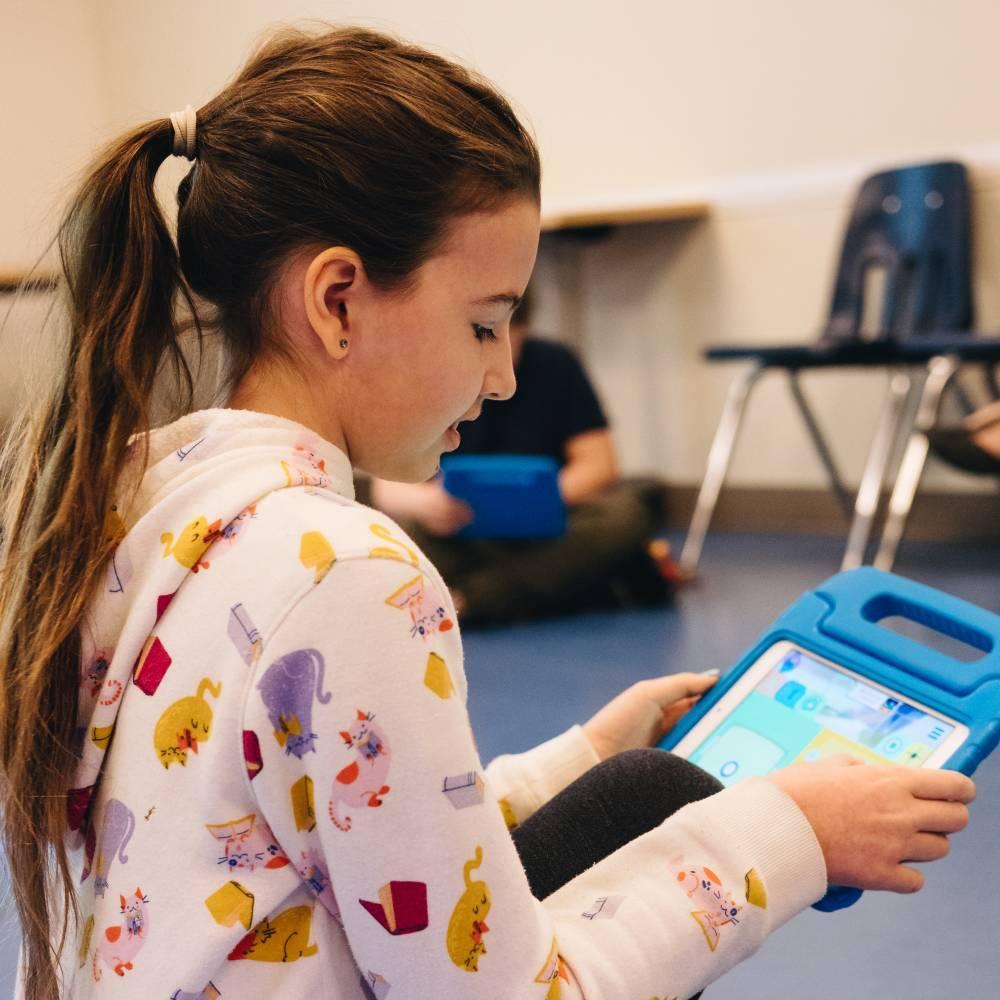 A tween girl uses an iPad during achildren's program.