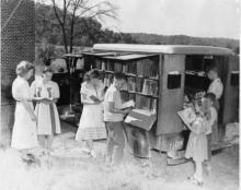Lois Henze, Bookmobile librarian, assists young patrons.